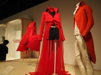 foreground: John Galliano for Maison Margiela/Spring 2015 posed next to garments from 18th century France; background: Comme des Garçons/Spring 2015